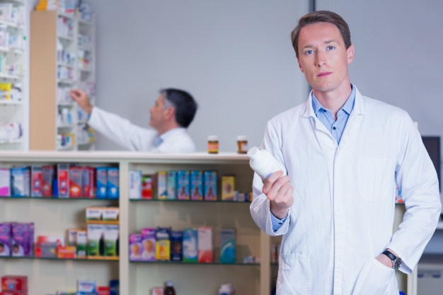 concentrating-doctor-holding-medicine-jar_13339-231816