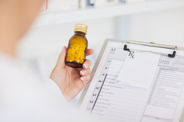 pharmacist-holding-drug-bottle-clipboard_13339-88188