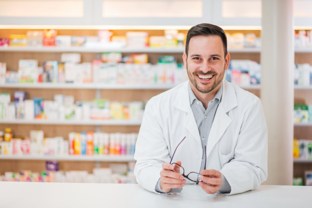 portrait-cheerful-handsome-pharmacist-leaning-counter-drugstore_109710-1738