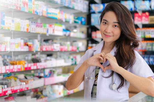 smiling-happy-asian-female-pharmacist-showing-heart-gesture-with-two-hands-pharmacy_51195-3811
