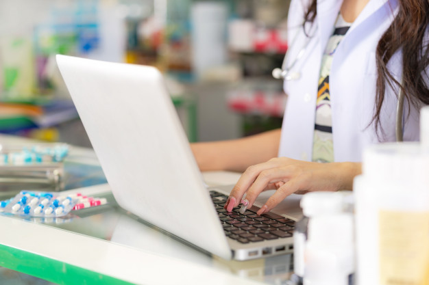 smiling-happy-asian-female-pharmacist-working-with-laptop-pharmacy_51195-3812 (1)