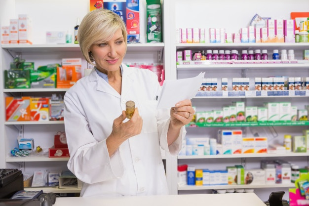 smiling-pharmacist-looking-prescription-medicine_13339-125271 (1)